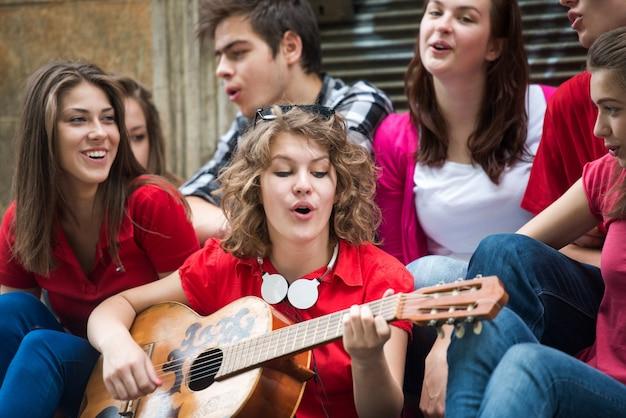 Szczęśliwa nastoletnia dziewczyna z gitarą