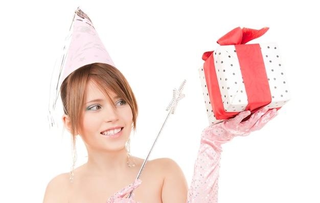 Szczęśliwa nastoletnia imprezowa dziewczyna z magiczną różdżką i pudełkiem na prezent