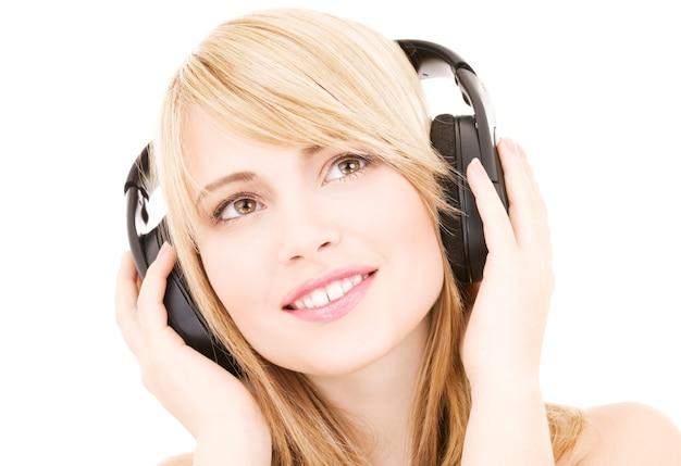 Szczęśliwa nastoletnia kobieta w słuchawkach na białym