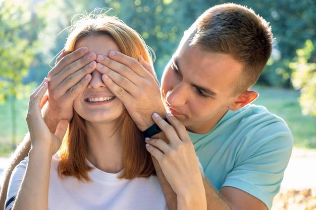 Szczęśliwa nastoletnia para ma zabawę wpólnie outdoors na zewnątrz w pogodnym lato parku zaskakuje each inny z zamykającymi oczami.