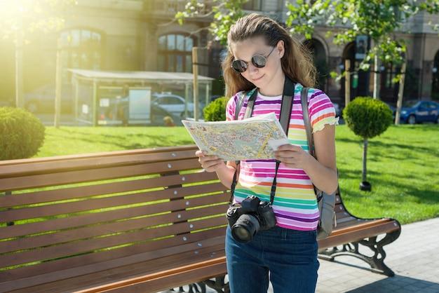 Szczęśliwa nastoletnia turystyczna podróży mienia kamera i mapa