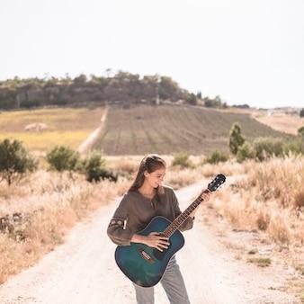 Szczęśliwa nastoletniej dziewczyny pozycja na drodze polnej bawić się gitarę