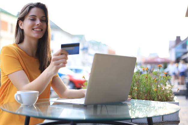 Szczęśliwa naturalna brunetka za pomocą karty kredytowej i laptopa w kawiarni na świeżym powietrzu.