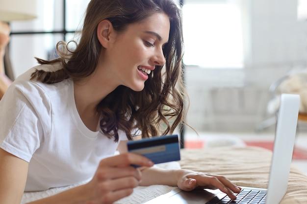 Szczęśliwa naturalna brunetka za pomocą karty kredytowej i laptopa w sypialni.