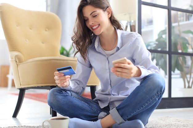 Szczęśliwa naturalna brunetka za pomocą karty kredytowej i telefonu komórkowego w sypialni.