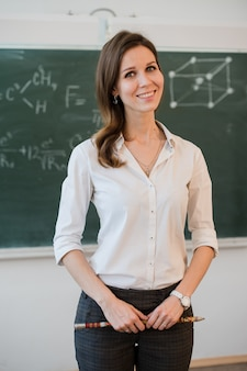 Szczęśliwa nauczyciel pozycja przed czerni deską