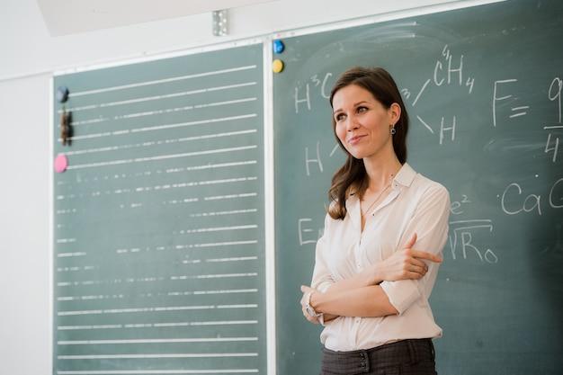 Szczęśliwa nauczycielka z rękami skrzyżowanymi stojąc przed zieloną deską