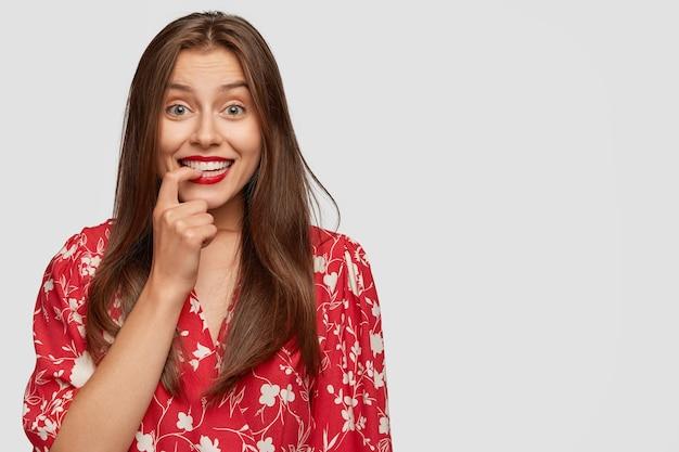 Szczęśliwa niedoświadczona bizneswoman uśmiecha się pozytywnie, trzyma palec na zębach