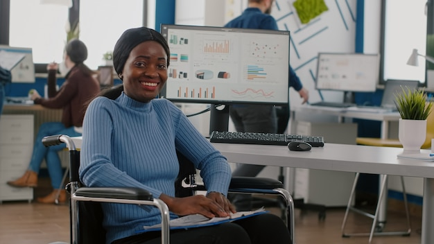 Szczęśliwa niepełnosprawna bizneswoman patrząca na kamerę uśmiechnięta w unieruchomionym, sparaliżowanym na wózku inwalidzkim w biurze gospodarczym firmy