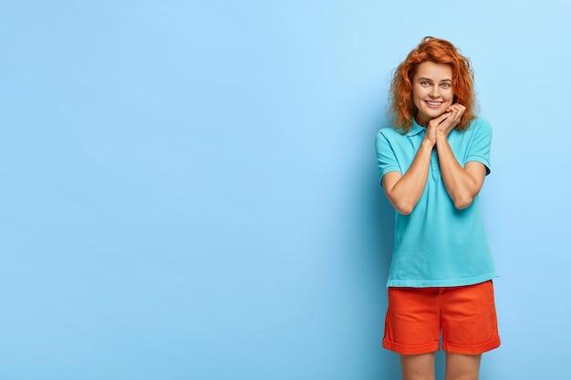 Szczęśliwa nieśmiała dziewczyna trzyma ręce przy twarzy, uśmiecha się delikatnie do kamery, patrzy z przyjemnością, ubrana swobodnie