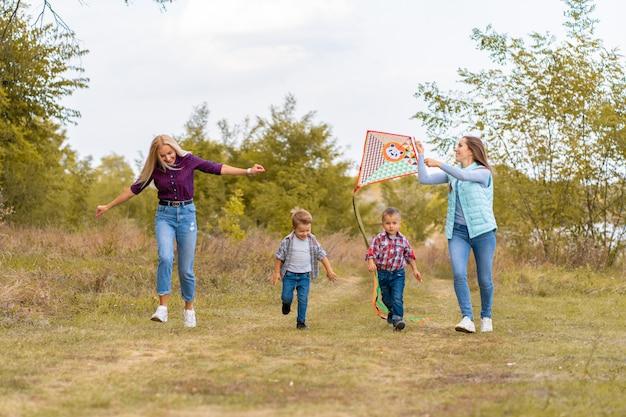 Szczęśliwa nietradycyjna rodzina dwójki młodych matek i ich dzieci wypuszcza latawiec o naturze o zachodzie słońca