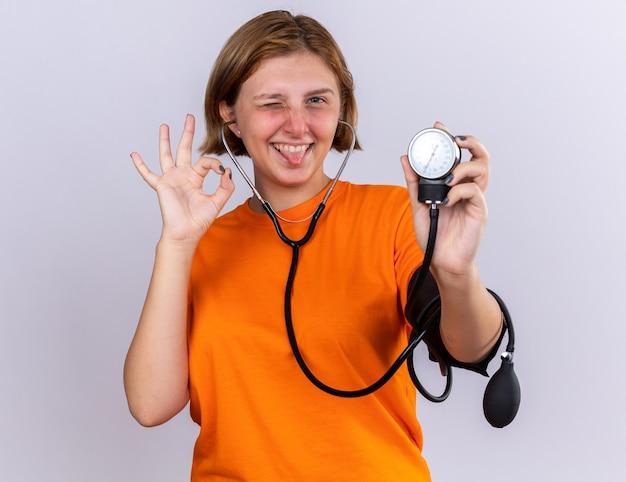 Szczęśliwa niezdrowa młoda kobieta w pomarańczowej koszulce pomiaru ciśnienia krwi za pomocą tonometru z uśmiechem na twarzy robi ok znak stojący nad białą ścianą