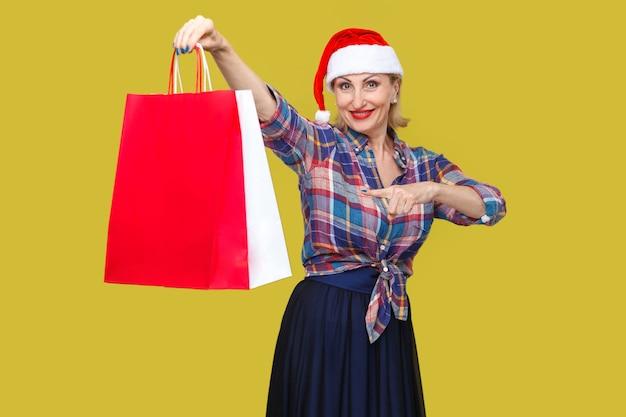 Szczęśliwa nowoczesna kobieta w średnim wieku w czerwonej czapce mikołaja i kraciastej koszuli stojącej, trzymającej i wskazującej palcem na torby na zakupy i uśmiechem toothy, patrząc na kamery. wewnątrz, strzał studyjny, żółte tło