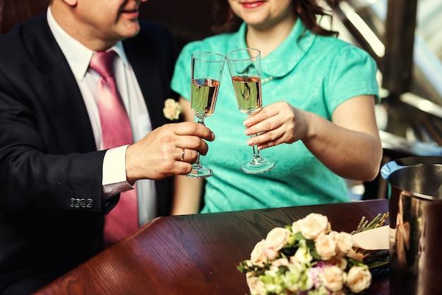Szczęśliwa nowożeńcy para pije białego ślubnego szampańskiego wino i bukiet