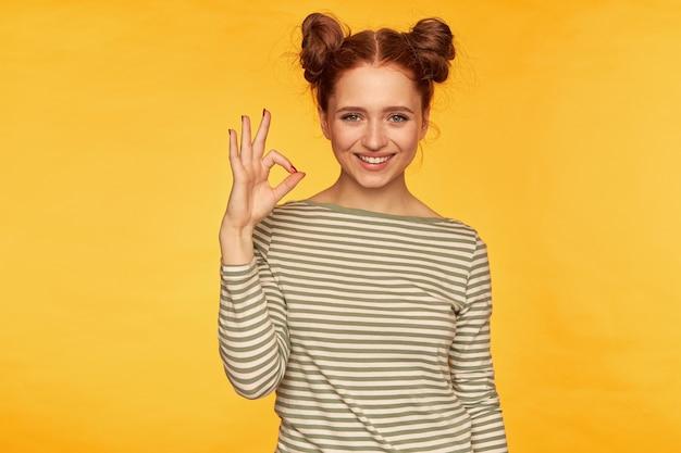 Szczęśliwa, odnosząca sukcesy kobieta o rudych włosach z dwoma bułeczkami. ubrany w pasiasty sweter i pokazujący znak porządku, uśmiechnięty