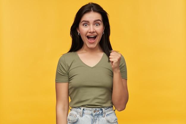 Szczęśliwa, odnosząca sukcesy młoda kobieta o ciemnych włosach w zwykłych ubraniach pokazująca gest zwycięzcy i krzycząca nad żółtą ścianą świętowanie zwycięstwa
