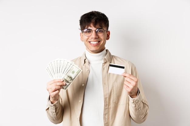 Szczęśliwa osoba stoi z pieniędzmi i plastikową kartą kredytową. młody człowiek pokazując gotówkę i uśmiechnięty zadowolony, stojąc na białej ścianie.