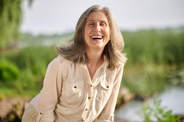 Szczęśliwa osoba. szczęśliwa uśmiechnięta uprzejma dorosła kobieta z siwymi włosami w stylowym jasnym garniturze na zewnątrz w pogodny dzień