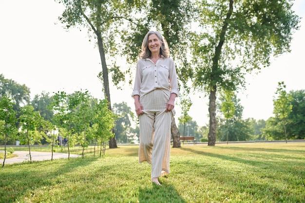 Szczęśliwa osoba. uśmiechnięta dorosła kobieta w lekkich spodniach i bluzce chodząca boso po trawie w parku w słoneczny dzień