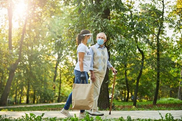 Szczęśliwa osoba w swobodnym ubraniu i ochronnej masce medycznej spacerująca po parku