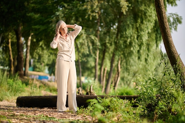 Szczęśliwa osoba. wesoła dorosła kobieta w lekkich spodniach i bluzce spaceruje na łonie natury w słoneczny dzień