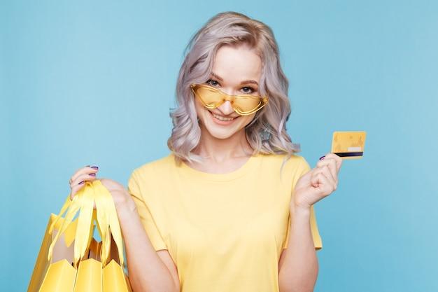 Szczęśliwa osoba z torbami na zakupy i kartą kredytową.