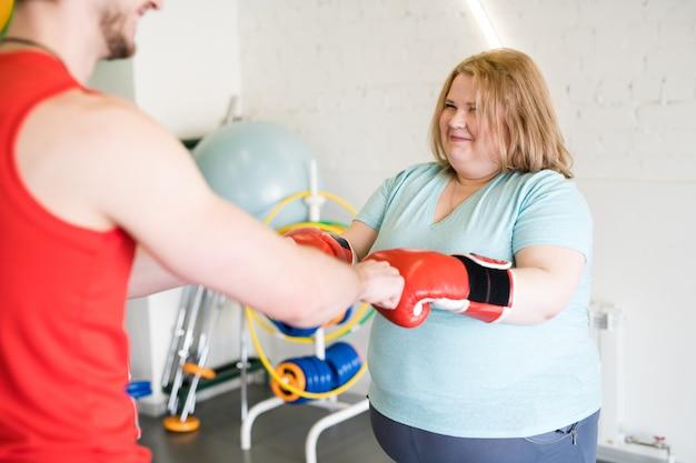 Szczęśliwa otyła kobieta pracująca z trenerem