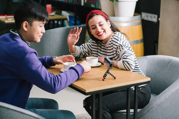 Szczęśliwa pani machająca i uśmiechająca się do kamery na statywie podczas picia kawy przy stole z młodym mężczyzną