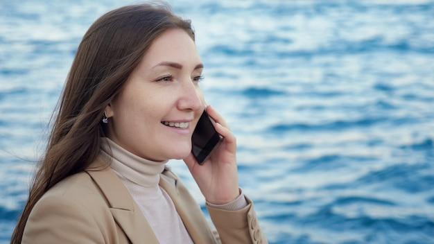 Szczęśliwa pani rozmawia na smartfonie stojącym na wybrzeżu przed rozmytym, głębokim, falującym morzem, ekstremalnym bliskim widokiem