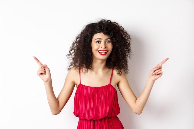 Szczęśliwa pani z kręconą fryzurą i czerwonymi ustami, uśmiechnięta biała zęby, wskazująca bokiem na dwa sposoby, odkładająca reklamy na bok, stojąca na białym tle.