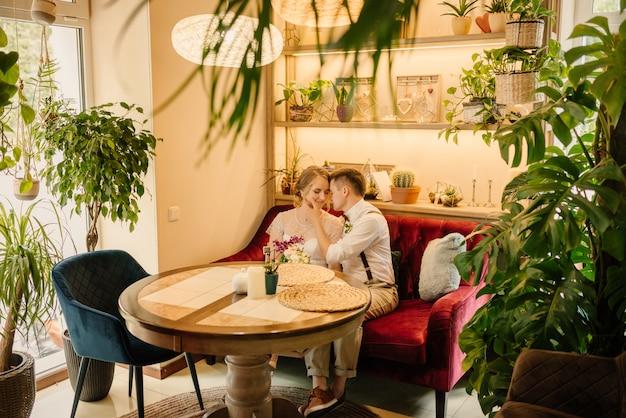 Szczęśliwa panna młoda i pan młody przytulanie. w dniu ślubu siedzą na kanapie w przytulnej kawiarni.