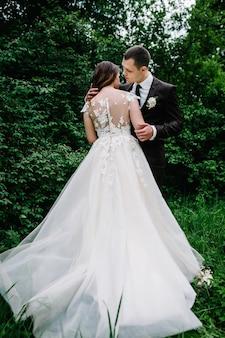Szczęśliwa panna młoda i pan młody ślub w zielonym lesie.
