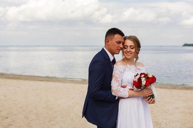 Szczęśliwa panna młoda i pan młody, spacery wzdłuż rzeki. romantyczny spacer nowożeńców po piaszczystej plaży w słoneczny dzień. para ślub na wybrzeżu morza. dzień ślubu na zewnątrz. uśmiechnięta panna młoda i groon, przytulanie i całowanie