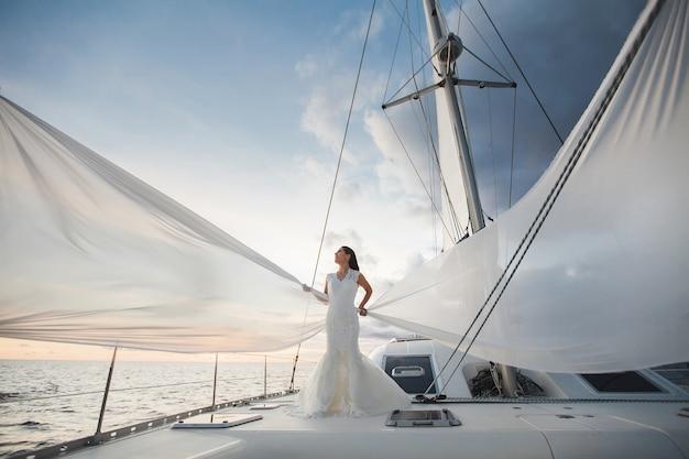 Szczęśliwa panna młoda na jachcie. wzdłuż wyspy płynie biały jacht z żaglem