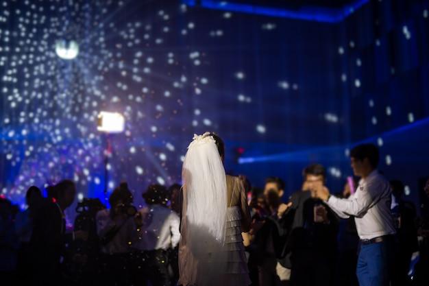 Szczęśliwa panna młoda tańczy na przyjęciu weselnym z gośćmi i oświetleniem ledowym w kolorze.