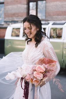 Szczęśliwa panna młoda uśmiecha się z bukietem kwiatów