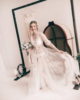 Szczęśliwa panna młoda w buduarowych sukienkach pokoju hotelowego