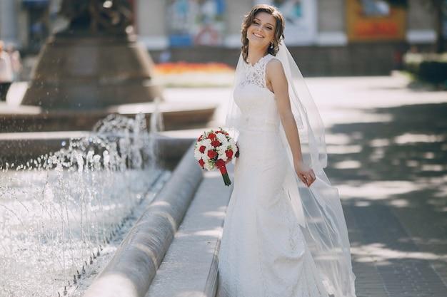Szczęśliwa panna młoda w pobliżu fontanny
