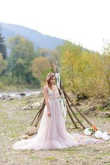 Szczęśliwa panna młoda w różowej sukni ślubnej. dziewczyna trzyma w rękach bukiet ślubny. ceremonia ślubna w stylu boho w pobliżu rzeki.