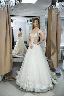 Szczęśliwa panna młoda w salonie pozowanie w sukni ślubnej