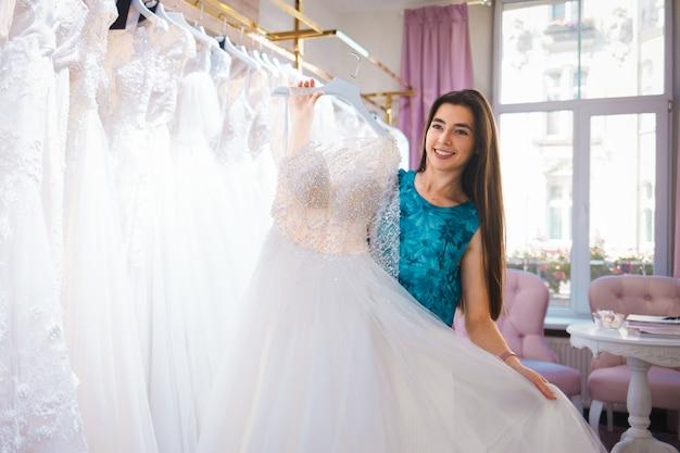 Szczęśliwa panna młoda wybiera sukienkę w butiku ślubnym