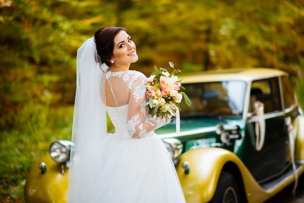 Szczęśliwa panna młoda z bukietem blisko ślubnego samochodu z kwiatami