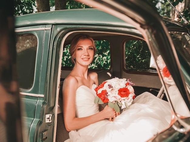 Szczęśliwa panna młoda z bukietem siedzi w samochodzie. ślub w stylu retro