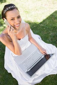 Szczęśliwa panna młoda z laptopem używać telefon komórkowego na trawie