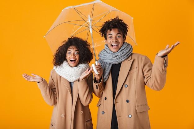Szczęśliwa para afrykańskich na sobie zimowe ubrania, stojąc pod parasolem na białym tle
