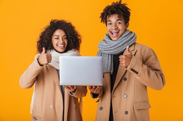 Szczęśliwa para afrykańskich noszenie zimowych ubrań stojących na białym tle, trzymając laptopa, kciuki do góry