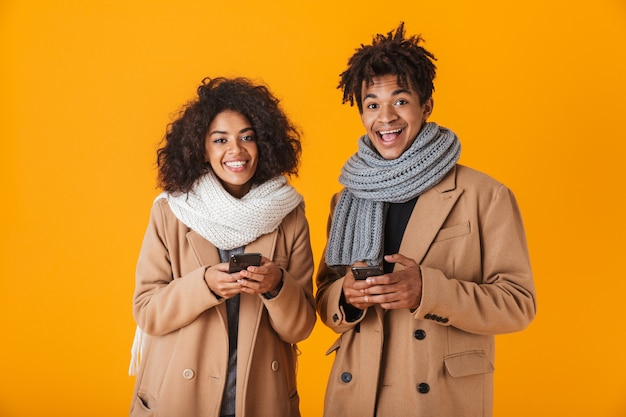 Szczęśliwa para afryki na sobie zimowe ubrania stojących na białym tle, przy użyciu telefonów komórkowych