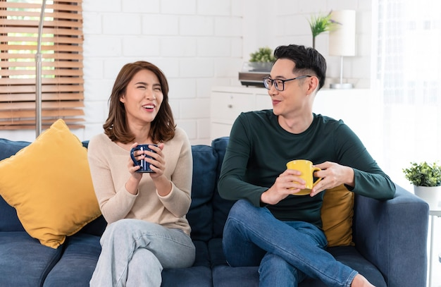 Szczęśliwa para azjatyckich mężczyzna i kobieta spędza weekend razem na kanapie w domu, relaksując się i ciesząc się piciem kawy.
