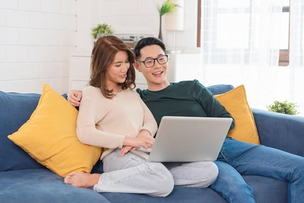 Szczęśliwa para azjatyckich mężczyzna i kobieta spędza weekend razem oglądając film na kanapie w pomieszczeniu w domu, relaksując się i ciesząc.