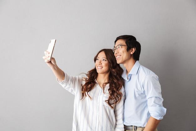 Szczęśliwa para azjatyckich stojących na białym tle, biorąc selfie z telefonu komórkowego
